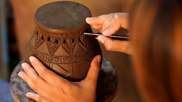 Hands make potter a decorative pattern on earthenware Premium Photo