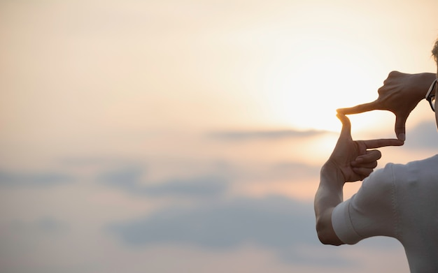 Hands making frame with sunset. close up of woman hands making frame gesture. Premium Photo