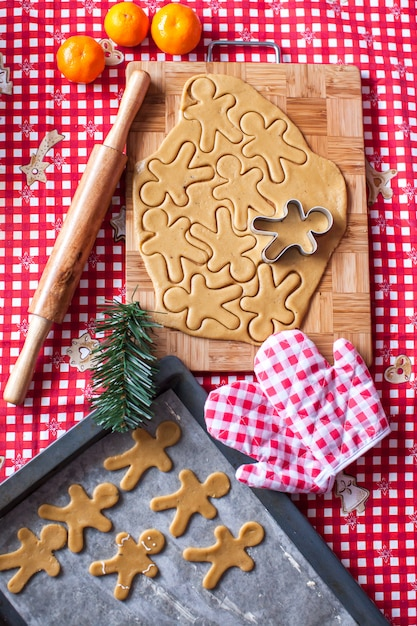 Hands making from dough christmas gingerbread man Premium Photo