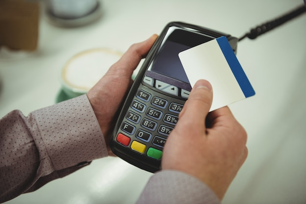 Hands making payment through credit card in cafe  hands making payment through credit card in cafe Free Photo
