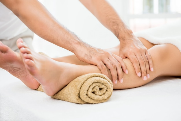 Hands of male therapist giving massage to a woman leg Premium Photo