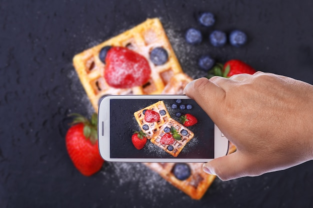 Hands of man with smartphone taking photo homemade traditional belgian waffles Premium Photo