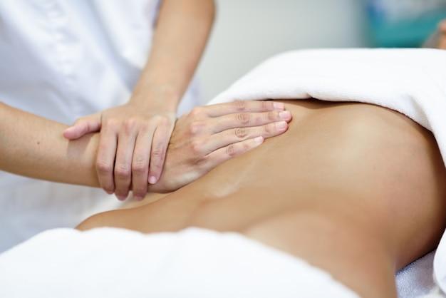 Hands massaging female abdomen.therapist applying pressure on belly. Free Photo