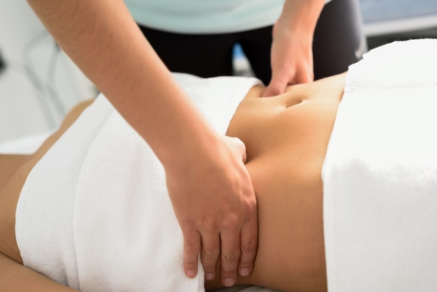 Hands massaging female abdomen.therapist applying pressure on belly. Free Photo