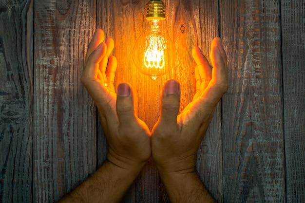 Руки рядом с зажженной лампочке Бесплатные Фотографии