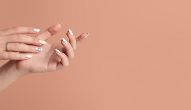 Руки красивой ухоженной женщины с женственными ногтями на бежевом фоне. Premium Фотографии