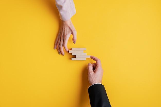 Руки бизнесмена и бизнес-леди укладывают деревянные колышки в концептуальном изображении стабильности бизнеса и совместной работы. Premium Фотографии