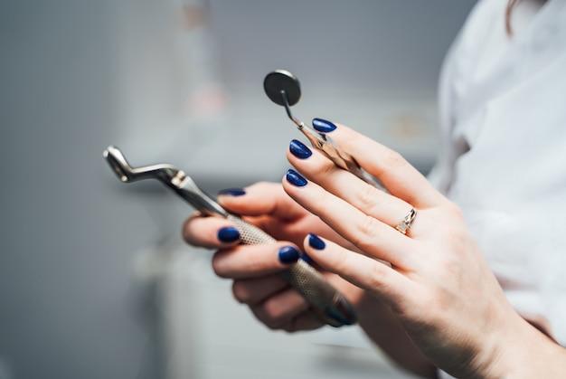 Руки стоматолога с голубыми ногтями держат инструменты пятен в клинике. медицинское оборудование в руках стоматолога Premium Фотографии