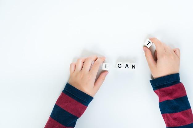 Руки маленького ребенка решили убрать пластиковый куб с буквы «т» от слова «я не могу» до «я могу» Premium Фотографии