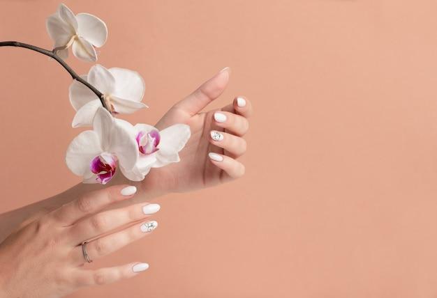Руки молодой женщины с белыми длинными ногтями на бежевом фоне с цветами орхидей. Premium Фотографии