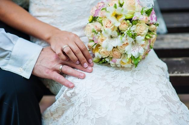 Руки жениха и невесты с кольцами на свадебный букет. Premium Фотографии