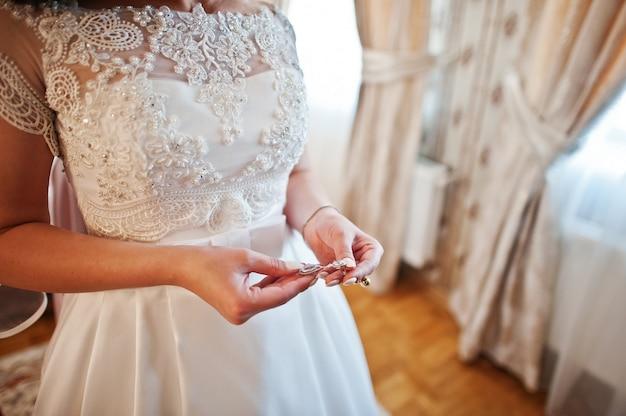 Руки невесты с серьгами на руках в день свадьбы Premium Фотографии