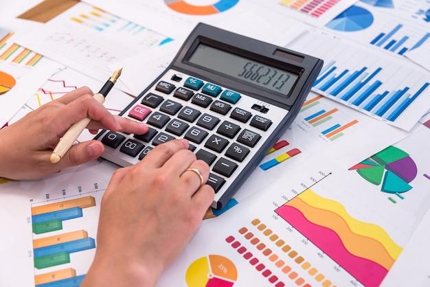 그래프와 다이어그램을 계산하는 비즈니스 분석가의 손 프리미엄 사진