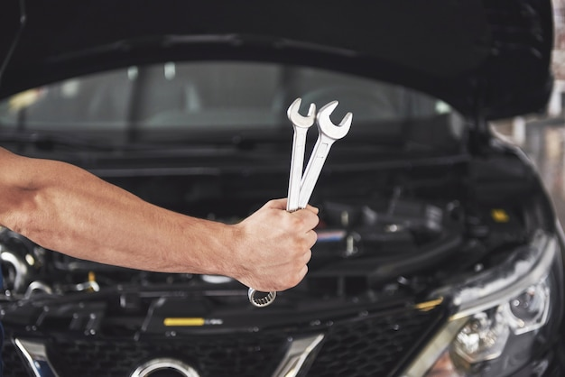 Руки автомеханика с гаечным ключом в гараже. Бесплатные Фотографии