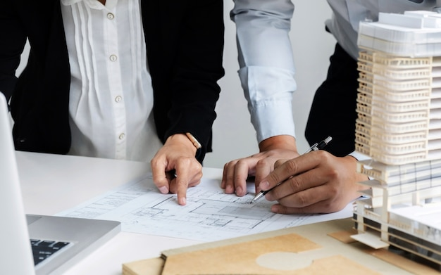 Hands of engineers working on blueprint at a workplace hands of engineers working on blueprint at a workplace construction and building concept premium photo malvernweather Image collections