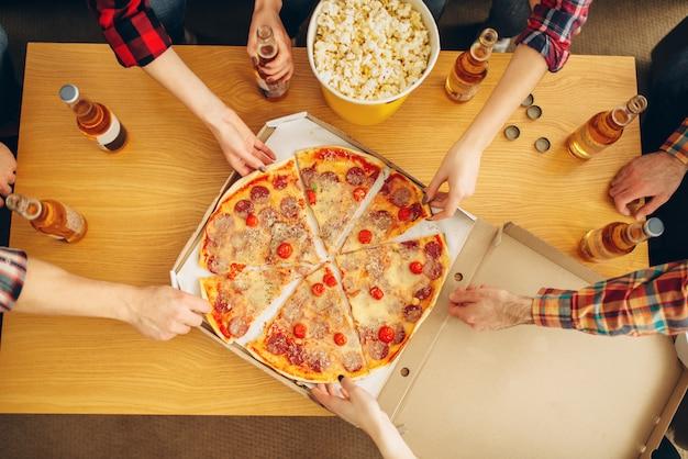 テーブル、上面図、ホームパーティーからピザのスライスを取る友人の手。 g Premium写真