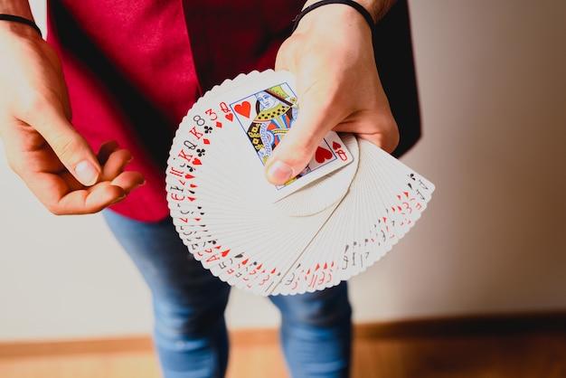 한 벌의 카드로 마술을하는 마술사의 손. 프리미엄 사진