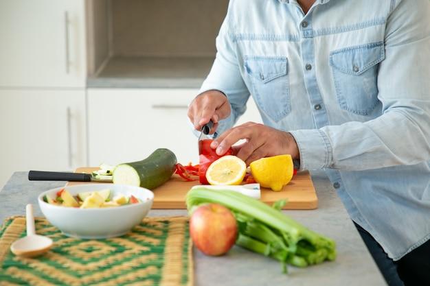 サラダを調理し、キッチンのまな板で新鮮な野菜を切る男の手。クロップショット、クローズアップ。健康食品のコンセプト 無料写真