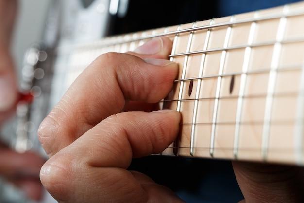 Руки человека, играющего на электрогитаре с красным крупным планом Premium Фотографии