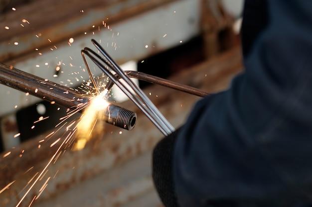 Руки человека, используя аргонную сварку для сварки металлических труб, искры летят во всех направлениях Premium Фотографии