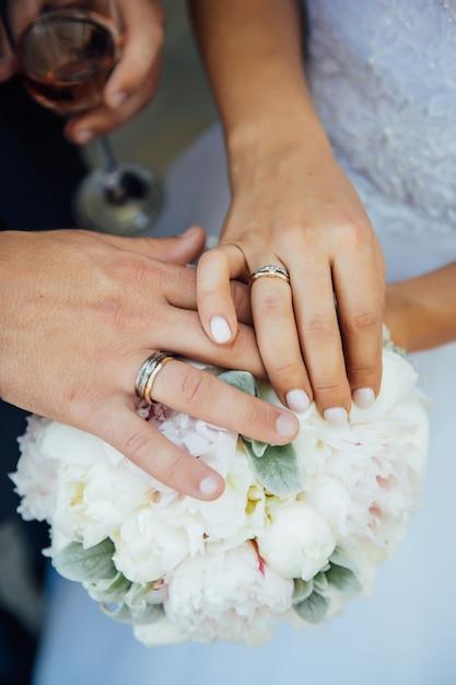 Руки молодоженов с обручальными кольцами - жених и невеста на свадебной церемонии. Premium Фотографии