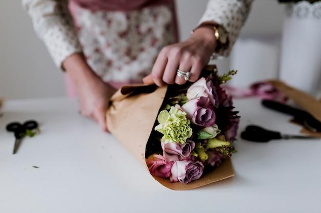 Руки женщины, обертывающей кучу бумаги Premium Фотографии