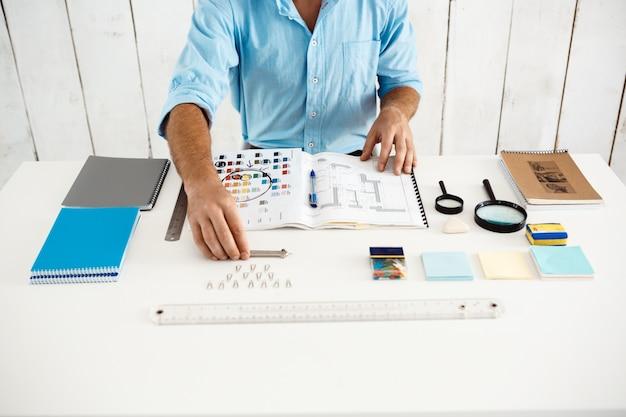 メモ帳でテーブルに座っている青年実業家の手 無料写真