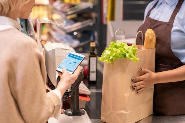 顧客が商品の支払いをしている間、パンとレタスの葉で紙袋を持っている若い女性のレジ係または店員の手 Premium写真