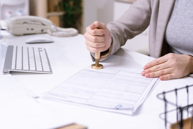 젊은 여성 회사원의 손에 책상에 앉아 고객에게 보내기 전에 재무 문서에 인감 프리미엄 사진