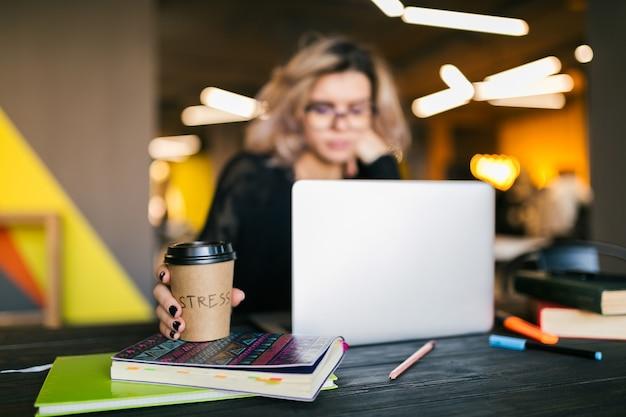 Руки молодой красивой женщины, сидя за столом в черной рубашке, работает на ноутбуке в офисе совместной работы, занятый студент фрилансер, пить кофе Бесплатные Фотографии
