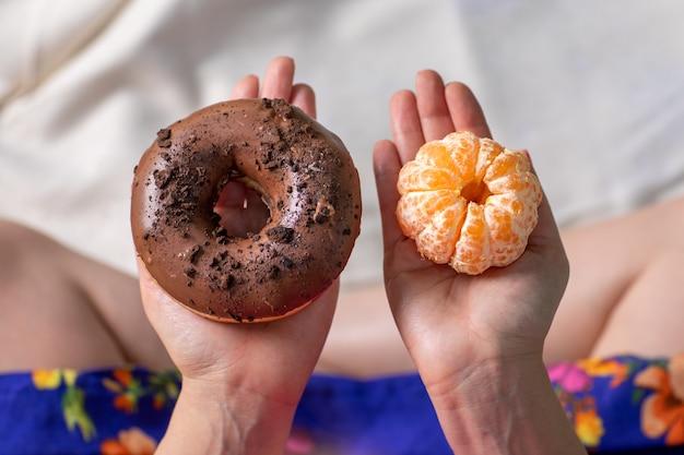 Руки молодой женщины на открытом воздухе под деревьями в парке, выбор между едой сладких пончиков или мандарина. калории или фрукты. Premium Фотографии