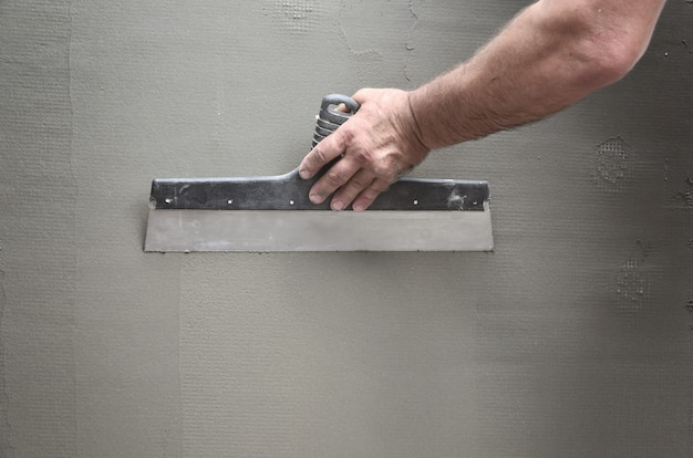 Hands of an old manual worker with wall plastering tools renovating house. Premium Photo