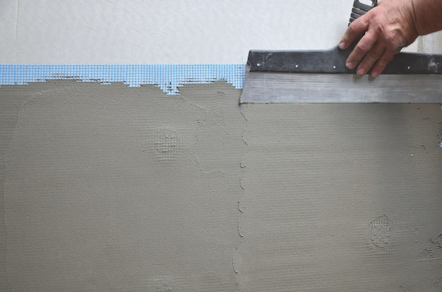 Hands of an old manual worker with wall plastering tools renovating house Premium Photo