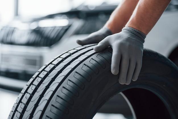 손만. 수리 차고에서 타이어를 들고 정비공. 겨울 및 여름 타이어 교체 무료 사진