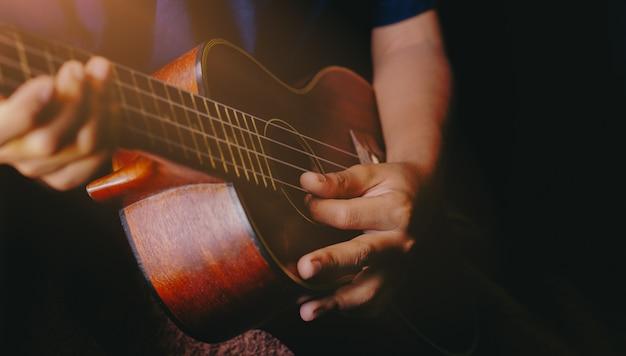 Hands playing acoustic ukulele guitar.music skills show Premium Photo