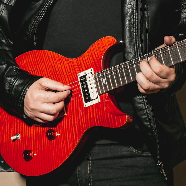Hands playing beautiful red guitar Free Photo