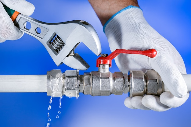 Hands plumber at work in a bathroom, plumbing repair service. leak of water. repair plumbing.