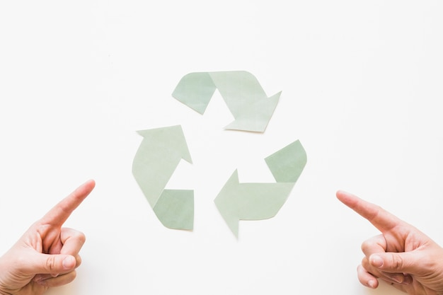 Hands pointing at recycle logo Free Photo