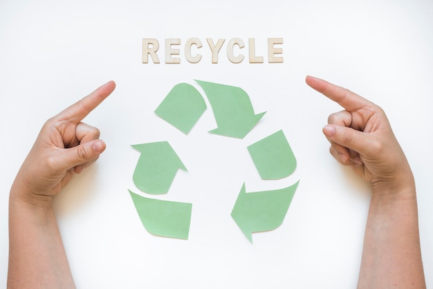 Hands pointing at recycle word with logo Free Photo