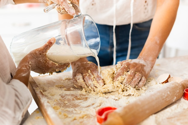 Hands pouring milk to prepare dough Free Photo