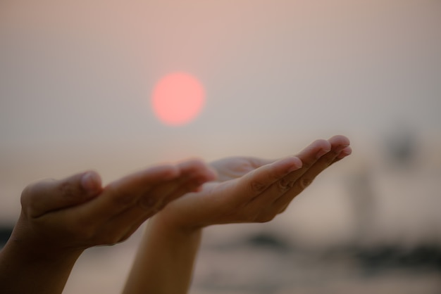 Hands praying for blessing from god during  sunset background. hope concept. Premium Photo