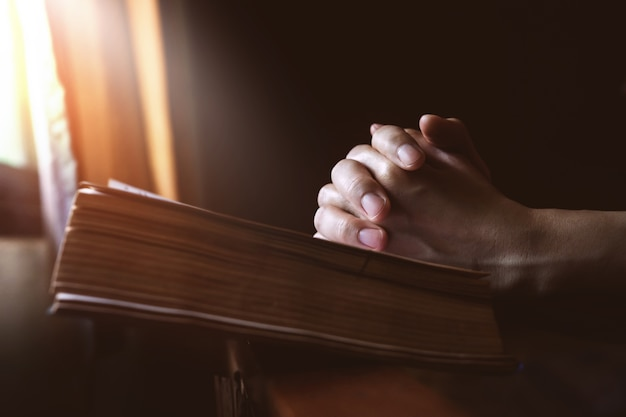 Hands praying on holy bible beside a window light Premium Photo