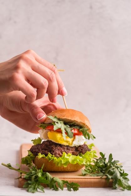 Hands preparing a big hamburger Free Photo