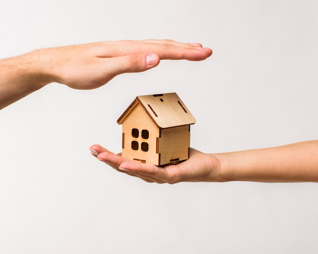 Hands protecting a wooden cottage Free Photo