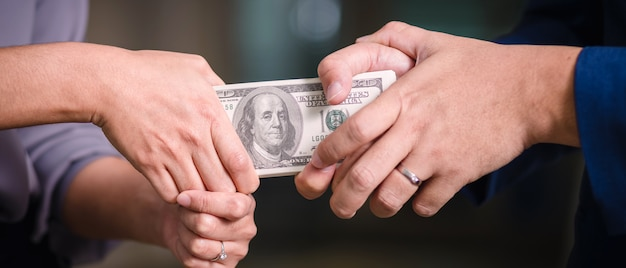 Hands pulling at stack of bank notes Premium Photo