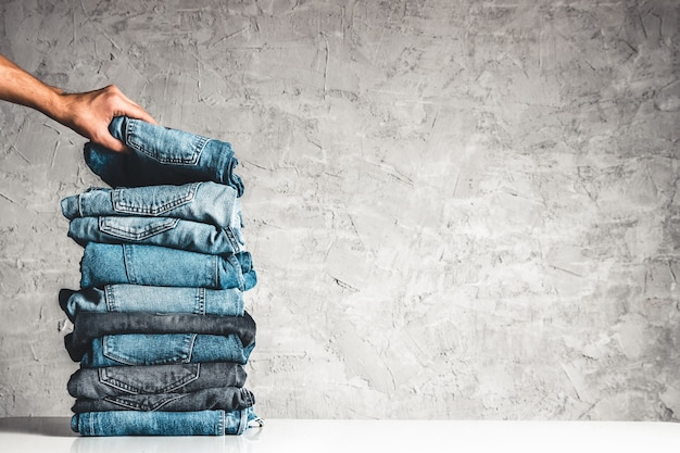 Hands, put the stack of blue jeans on gray background. Premium Photo