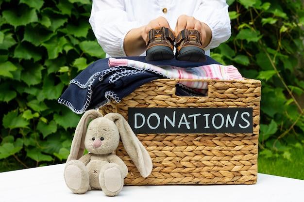 Руки кладут детскую обувь в ящик для пожертвований Premium Фотографии
