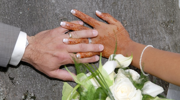 Hands and rings on wedding bouquet Premium Photo