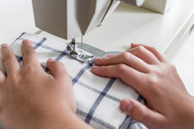 Hands of a seamstress on a sewing machine in the process of sewing with a copy of the space Premium Photo