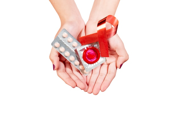 Hands showing wrapped condom and contraceptive medicine with red awareness ribbon Premium Photo